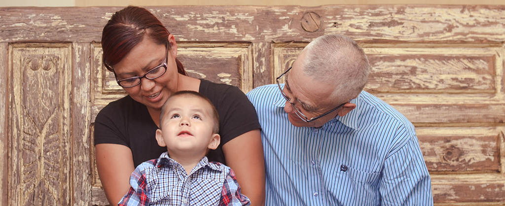 family with young boy sitting and smiling at rmhc-nm house