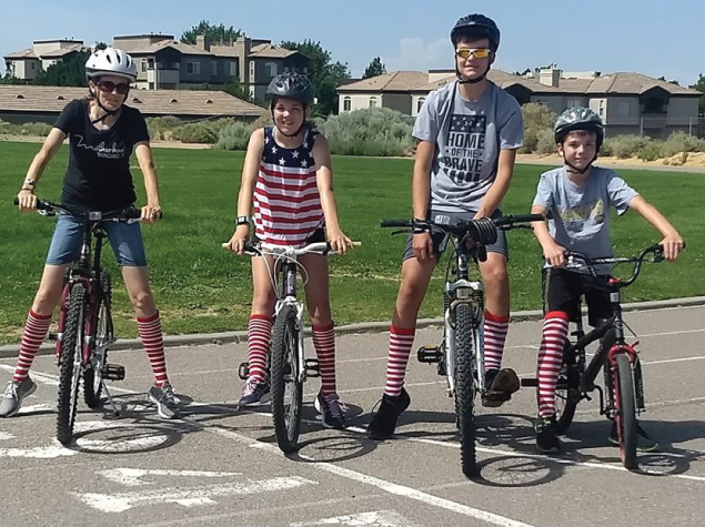 family on a group bike ride with matching red and white striped socks for virtual 5k