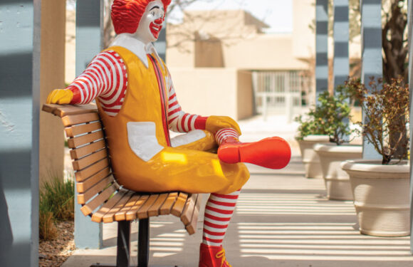 ronald mcdonald statue sitting on bench in friendly manner with smile and outstretched arm in comfort and support