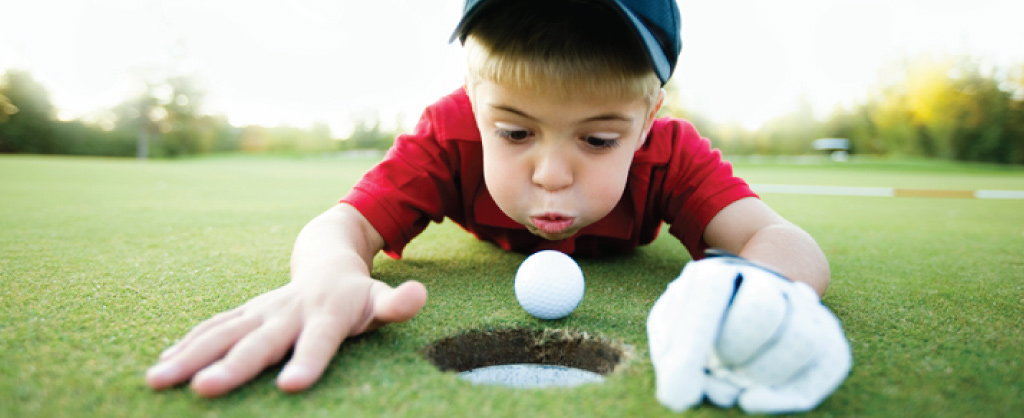 young boy playing golf close to the hole blowing against ball close to cup