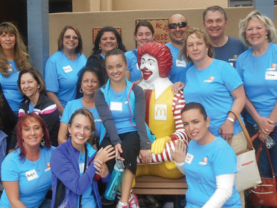 group of volunteers taking group picture with ronald mcdonald statue