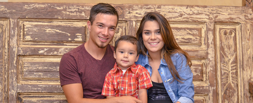 young family with young son smiling for family picture